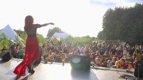 Meisje in het rode kleding zingen in microfoon op stadium voor menigte van mensen, overleg in openlucht stock footage
