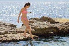 Meisje in het roze bikini voorzichtige lopen langs rots royalty-vrije stock foto