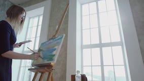 Meisje het schilderen overzees op een canvas stock videobeelden
