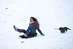 Meisje het sledging met haar hond Royalty-vrije Stock Foto's