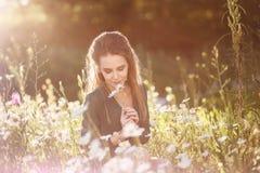 Meisje het snuiven kamillebloemen op een bloemgebied stock afbeelding