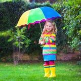 Meisje het spelen in de regen onder kleurrijke paraplu Stock Afbeeldingen