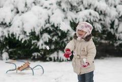 Meisje het spelen in de sneeuw en werpt sneeuwballen Stock Afbeelding