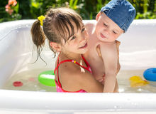 Meisje het spelen in een opblaasbare pool met zijn jongere broer Stock Fotografie
