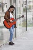 Meisje het spelen gitaar in de stad stock afbeelding