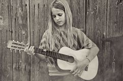 Meisje het spelen gitaar door schuur in mist Stock Fotografie