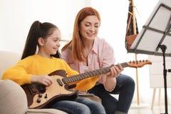 Meisje het spelen gitaar met haar leraar bij muziekles royalty-vrije stock foto's