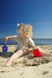Meisje het spelen in het zand op het strand door het overzees royalty-vrije stock afbeeldingen
