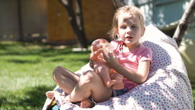 Meisje het spelen met baby - pop in binnenplaats stock footage