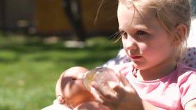 Meisje het spelen met baby - pop in binnenplaats stock video