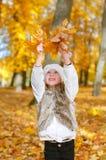 Meisje het spelen met bladeren. Royalty-vrije Stock Foto's