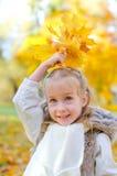 Meisje het spelen met bladeren. Stock Afbeelding