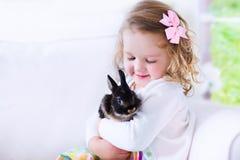 Meisje het spelen met een konijn royalty-vrije stock afbeeldingen
