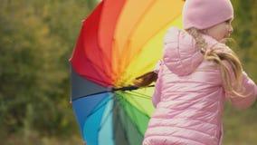 Meisje het spelen met een multi-colored paraplu stock video