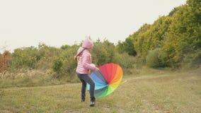 Meisje het spelen met een multi-colored paraplu stock footage