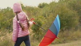 Meisje het spelen met een multi-colored paraplu stock videobeelden
