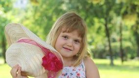 Meisje het spelen met een strohoed, de verwijdering van het uit haar gezicht en het glimlachen; langzame motie stock videobeelden