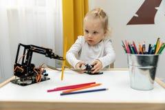 Meisje het spelen met elektronisch robotwapen thuis stock fotografie