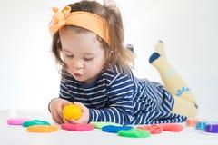 Meisje het spelen met gekleurde die plasticine op de witte achtergrond wordt geïsoleerd stock fotografie