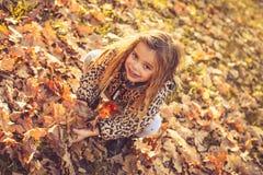 meisje het spelen met gevallen bladeren royalty-vrije stock afbeeldingen