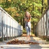 Meisje het spelen met gevallen bladeren Stock Afbeeldingen