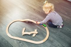 Meisje het spelen met houten spoorweg op vloer royalty-vrije stock afbeeldingen