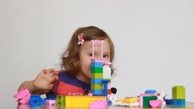 Meisje het spelen met kleurrijke kleine blokken van een aannemer Het kind ontwikkelt zijn het denken vaardigheden ontwikkeling stock footage
