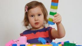 Meisje het spelen met kleurrijke kleine blokken van een aannemer Het kind ontwikkelt zijn het denken vaardigheden vermaak stock footage