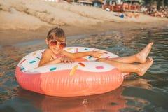 Meisje het spelen met opblaasbare ring in water stock afbeelding