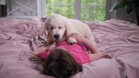 Meisje het spelen met puppyhuisdier die op bed liggen stock videobeelden