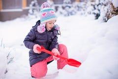 Meisje het spelen met rode schop in de tuin stock afbeelding