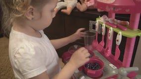 Meisje het spelen met roze stuk speelgoed keuken stock videobeelden
