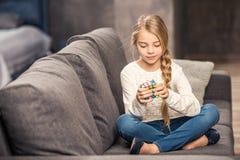 Meisje het spelen met rubik` s kubus stock afbeelding