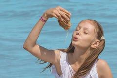 Meisje het spelen met shell op de overzeese achtergrond royalty-vrije stock foto