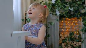 Meisje het spelen met wit houten hobbelpaard stock footage