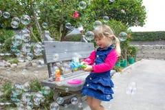 Meisje het spelen met zeepbels in de tuin stock foto's