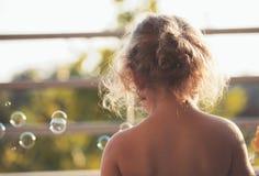 Meisje het spelen met zeepbels in openlucht op een warme de zomerdag - de Zomertijd die het concept van het pretkind hebben royalty-vrije stock afbeelding
