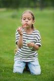 Meisje het spelen met zeepbels terwijl het zitten op groene weide royalty-vrije stock foto