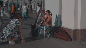 Meisje het spelen op de straatharp, straatmusicus stock video