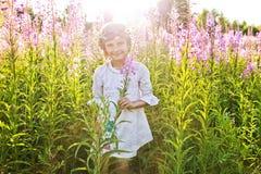 Meisje het spelen op een gebied van bloemen stock afbeeldingen