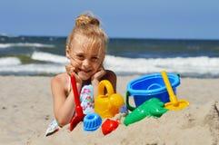 Meisje het spelen op het zandstrand Royalty-vrije Stock Afbeeldingen