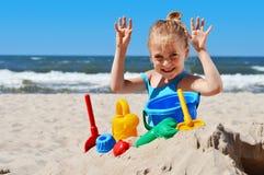 Meisje het spelen op het zandstrand Stock Afbeeldingen