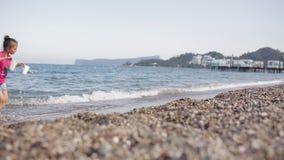 Meisje het spelen op het strand met kiezelstenen stock video