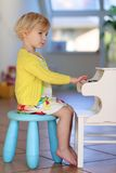 Meisje het spelen piano binnen Stock Afbeelding