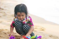Meisje het spelen stuk speelgoed op strand Stock Afbeelding