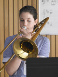 Meisje het Spelen Trombone in Muziekklasse stock fotografie