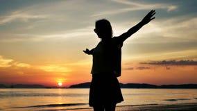 Meisje het spinnen in langzame motie bij zonsondergang op een tropisch strand stock video