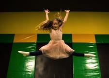 Meisje het springen op een trampoline en het maken van streng verdelen in spelruimte voor jonge geitjes stock afbeeldingen