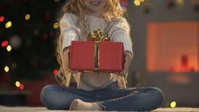 Meisje het standhouden Kerstmis huidig aan camera, vakantiedecoratie het fonkelen stock video