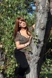 Meisje het stellen naast de boom Stock Afbeeldingen
